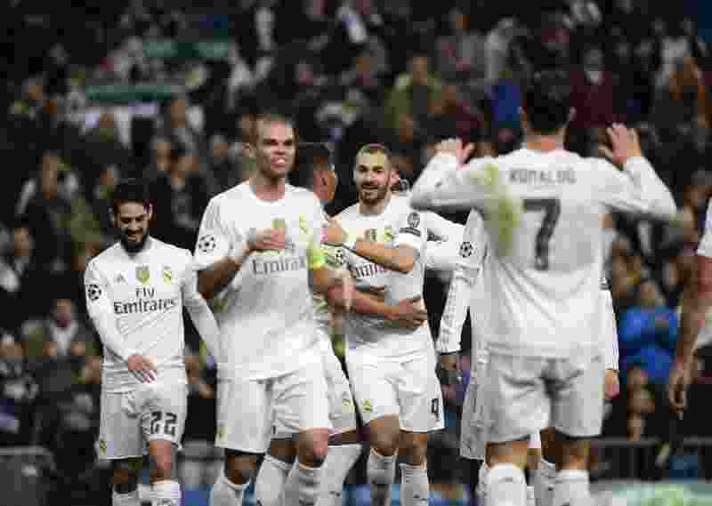 Real Madrid's French forward Karim Benzema (C) celebrates with teammates after scoring during the UEFA Champions League Group A football match Real Madrid CF vs Malmo FF at the Santiago Bernabeu stadium in Madrid on December 8, 2015.   AFP PHOTO/ PIERRE-PHILIPPE MARCOU / AFP / PIERRE-PHILIPPE MARCOU