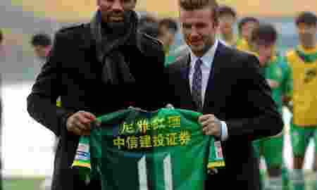 BEIJING, CHINA - MARCH 21: British soccer player David Beckham (R) is presented a jersey by Beijing Guo'an Soccer Club's footballer Frederic Oumar Kanoute on March 21, 2013 in Beijing, China.  Beckham visited the club as the ambassador for the youth football program in China and the Chinese Super League Thursday.  PHOTOGRAPH BY Xinhua /Landov / Barcroft Media  UK Office, London. T +44 845 370 2233 W www.barcroftmedia.com  USA Office, New York City. T +1 212 796 2458 W www.barcroftusa.com  Indian Office, Delhi. T +91 11 4053 2429 W www.barcroftindia.com