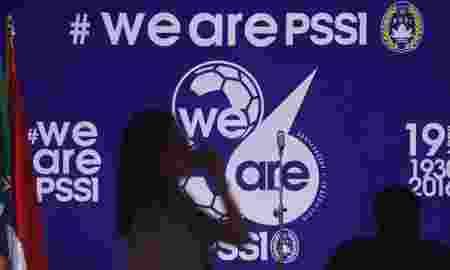 """Seorang perempuan melintasi backdrop bertuliskan """"We are PSSI"""" ketika syukuran HUT ke-86 PSSI di Stadion Utama Gelora Bung Karno, Jakarta, Selasa (19/4). Perayaan HUT ke-86 PSSI mengangkat tema """"We are PSSI"""" dilaksanakan secara sederhana ditengah kondisi sepak bola Indonesia dalam kondisi mati suri karena sanksi FIFA. ANTARA FOTO/Wahyu Putro A/pd/16"""