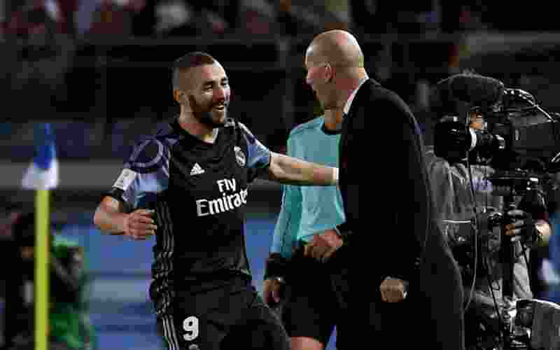 Real Madrid's forward Karim Benzema (L) celebrates his goal with head coach Zinedine Zidane (R) during the Club World Cup semi-final football match between Mexico's Club America and Spain's Real Madrid at Yokohama International stadium in Yokohama on December 15, 2016. / AFP PHOTO / TOSHIFUMI KITAMURA